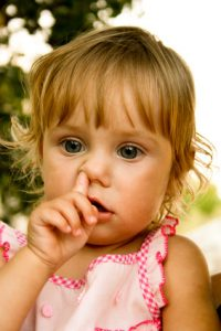 Little girl picking his nose